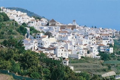 A view of a glistening, whitewashed Frigiliana in the Spanish sun.