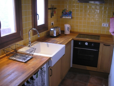 Closer view of the main kitchen work area showing large country style porcelain sink.